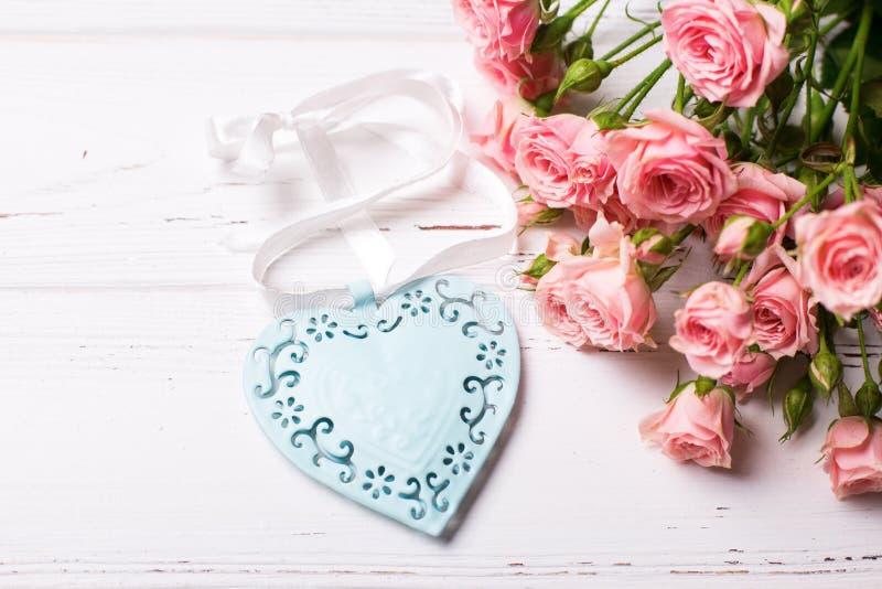 Голубое декоративное сердце и розовые розы цветут на белом деревянном ба стоковое изображение rf
