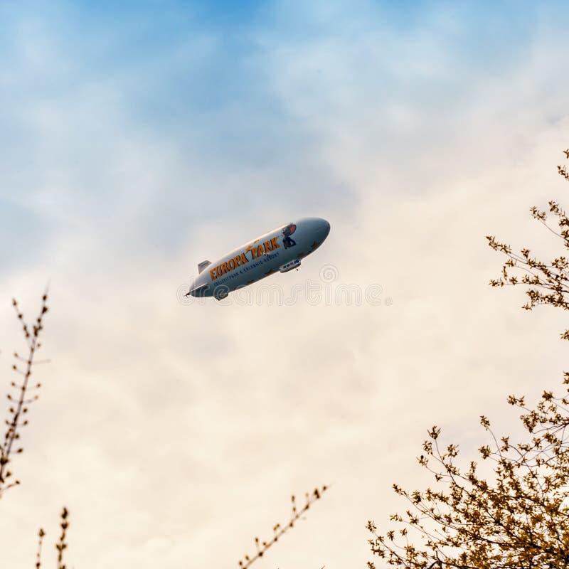 Голубое дирижабельное летание в облачном небе стоковое изображение