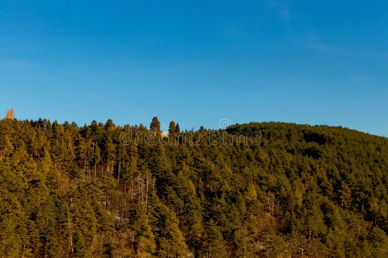 Голубое небо и высокая гора в деревьях других цветов, дом стоковые изображения