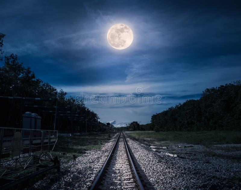 Голубое небо и полнолуние над силуэтами деревьев и железной дороги стоковое изображение rf