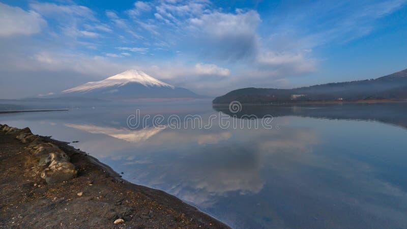Голубое небо утра и белое облако с крышкой снега устанавливают Фудзи отражая на озере Yamanaka стоковое изображение rf