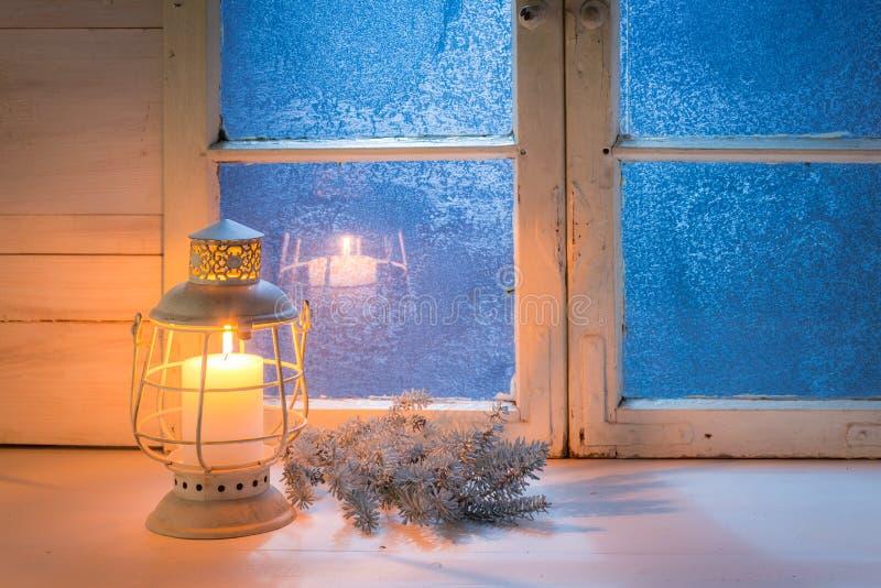 Голубое окно на ноче и горя свеча для рождества стоковые фотографии rf