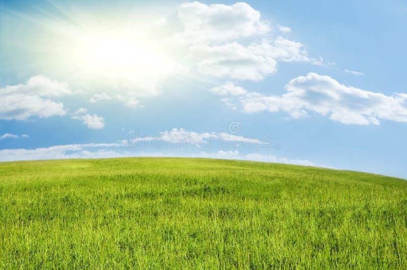 голубое пасмурное солнце неба зеленого холма под whit стоковые изображения