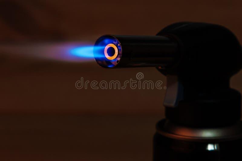 Голубое пламя с ручной газовой горелкой с черной предпосылкой стоковое фото