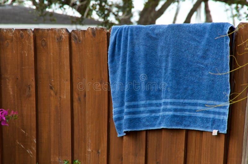 Голубое пляжный полотенце вися на загородке стоковая фотография rf