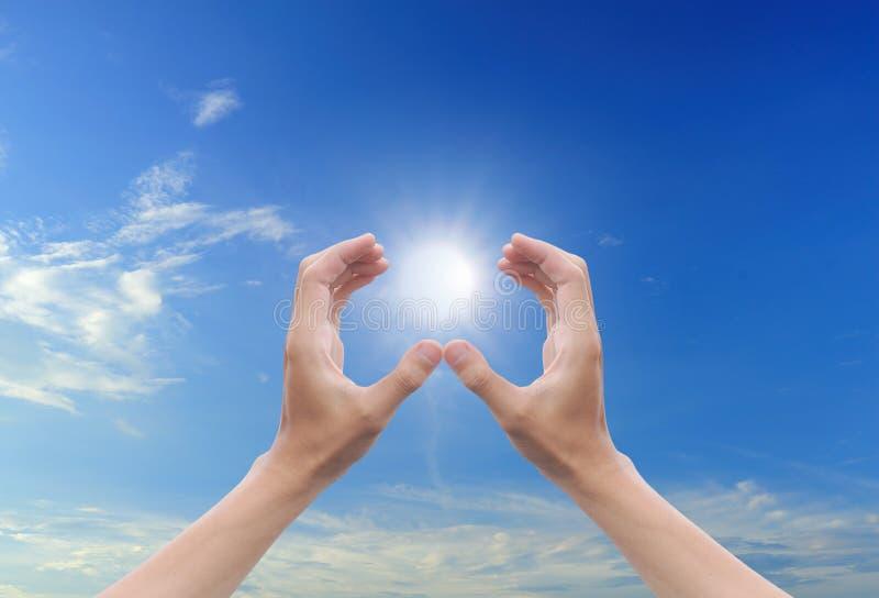 голубое солнце неба руки стоковая фотография
