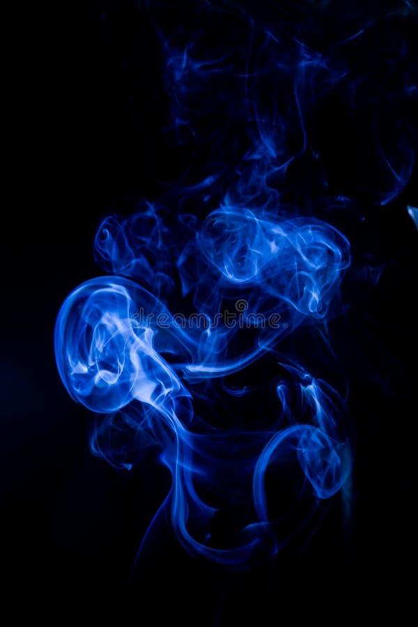 Голубое токсическое движение перегаров на черной предпосылке стоковые изображения