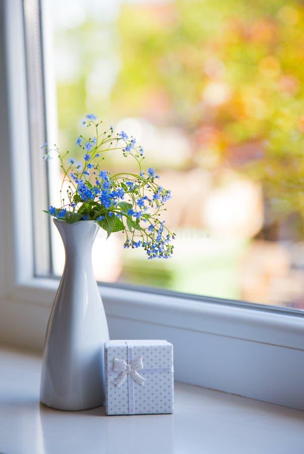 Голубое Brunnera цветет в белой вазе с подарочной коробкой около окна стоковые изображения rf