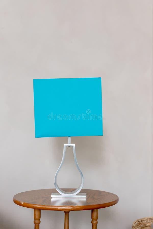 Голубой абажур изолированный на бежевой предпосылке стены Настольная лампа в бирюзе и серых цветах живущая самомоднейшая комната  стоковые изображения rf