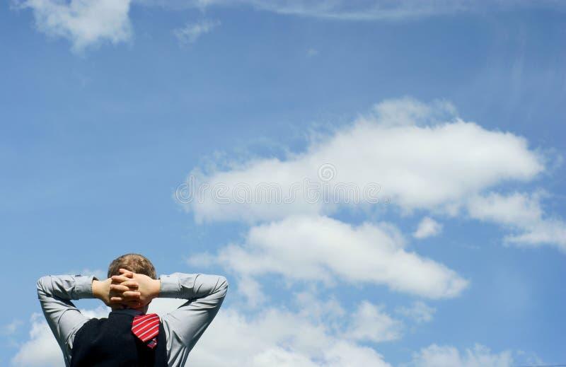 голубой бизнесмен ослабляет небо стоковое изображение rf