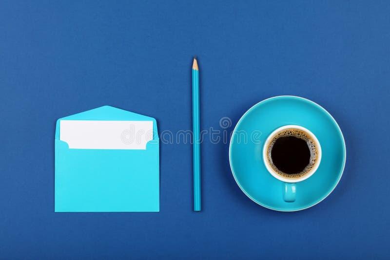 Голубой бумажный конверт письма и кофейная чашка стоковые изображения rf