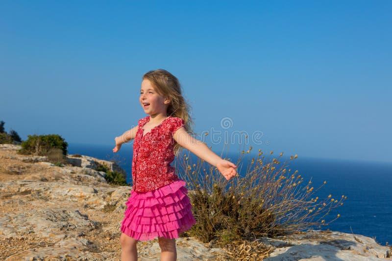 Голубой день с руками девушки малыша открытыми к ветру стоковая фотография