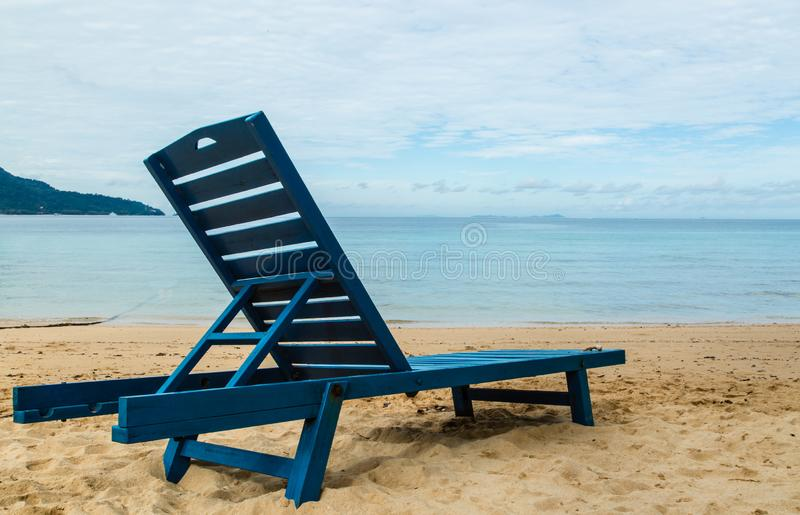 Голубой деревянный стул на стороне песков к голубому морю стоковые изображения