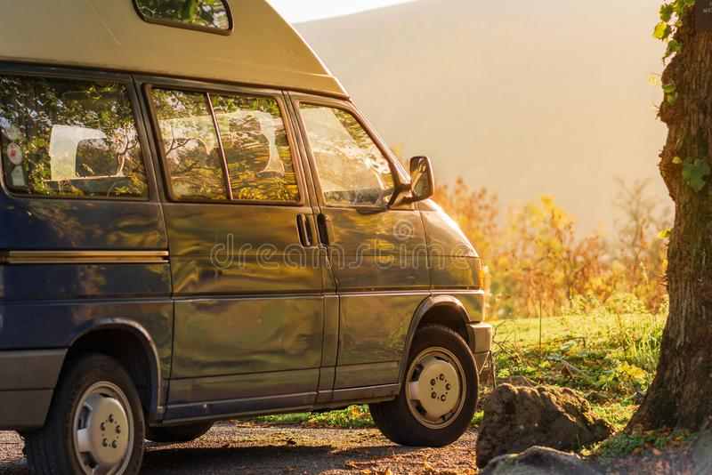 Голубой жилой фургон сидит на заходе солнца против яркого ого-зелен луга с сочным оранжевым солнечным светом течь внутри стоковые изображения rf