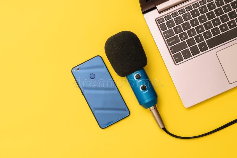 Голубой и голубой микрофон смартфона около ноутбука на желтой предпосылке Концепция организации рабочего места стоковое изображение rf