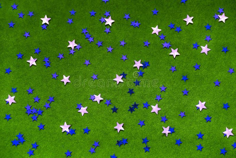 Голубой и серебряный сверкнают звезды на яркой ой-зелен предпосылке стоковое изображение