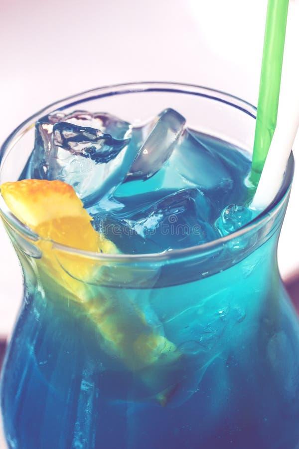 Голубой коктейль лагуны с голубыми настойкой, водкой, лимонным соком и содой curacao, украшенными с оранжевым куском стоковое фото
