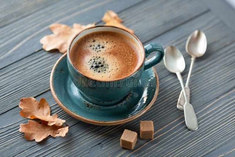 Голубой кофе whith чашки, связанный свитер, листья осени на деревянной предпосылке стоковая фотография rf