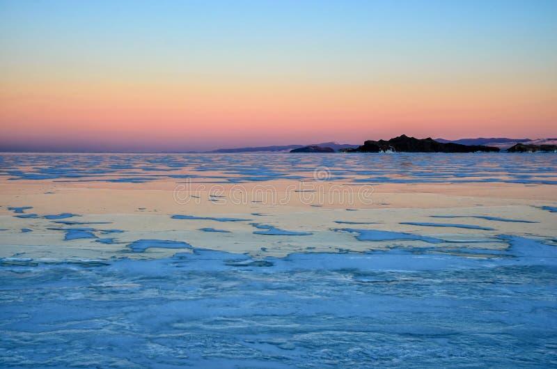 Голубой лед озера Байкал под розовым небом захода солнца стоковое изображение
