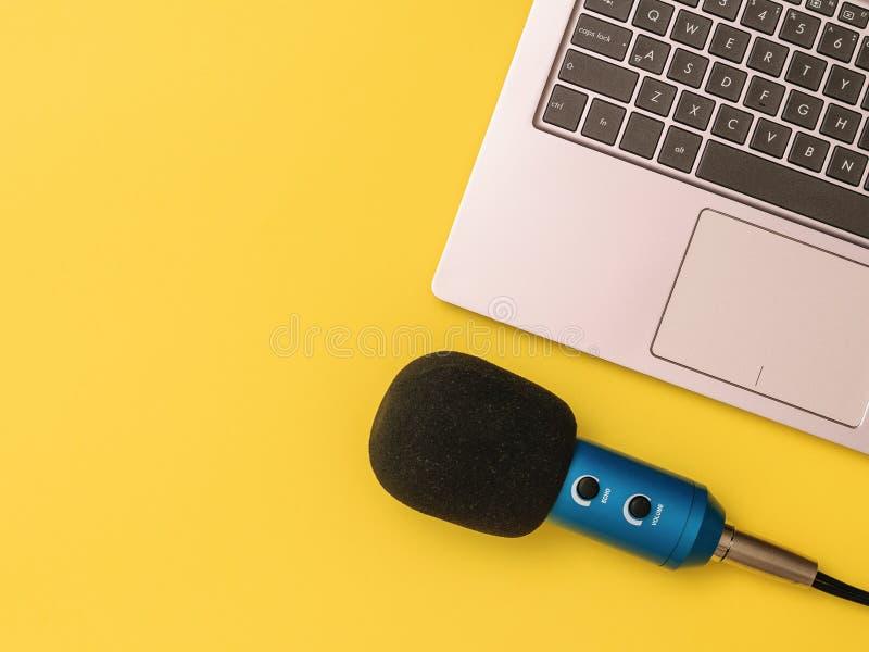 Голубой микрофон подключенный с ноутбуком на желтой предпосылке Концепция организации рабочего места стоковые изображения rf