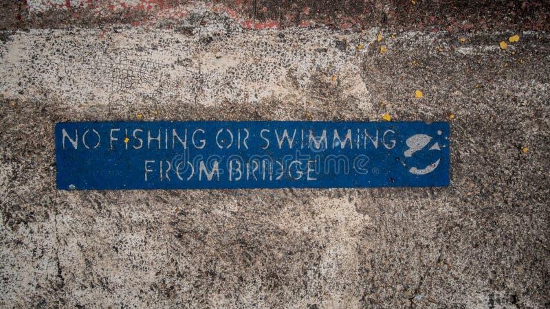 Голубой отсутствие рыбной ловли или плавать от знака моста на выдержанном, достигшем возраста бетоне стоковые изображения