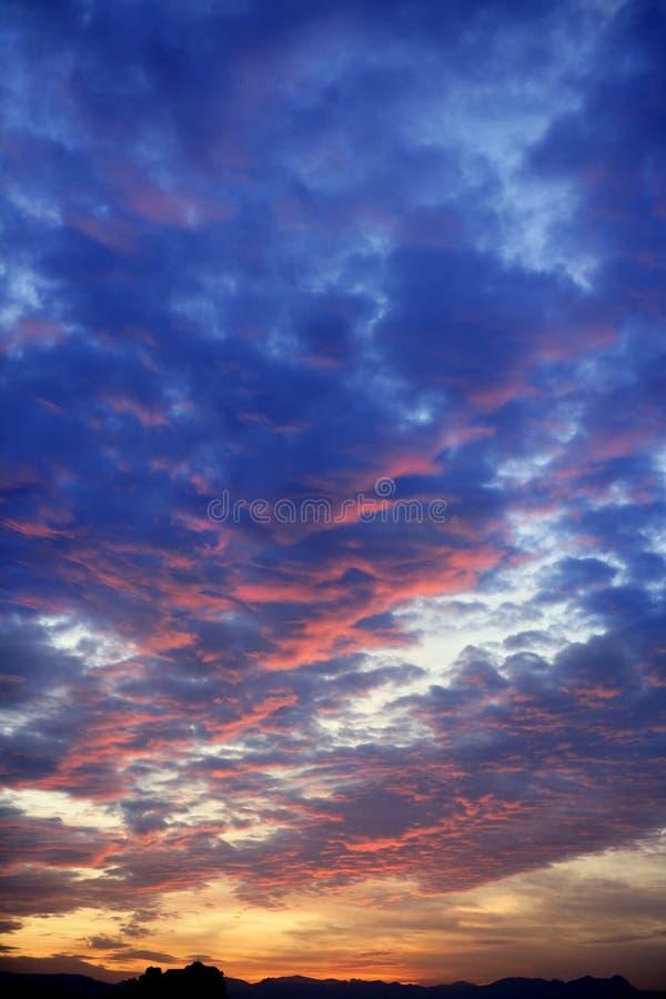 голубой пасмурный цветастый красный заход солнца неба стоковая фотография rf