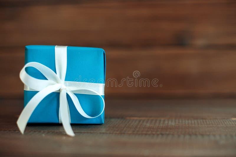 Голубой подарок с лентой на деревянной предпосылке Концепция holida стоковые фотографии rf