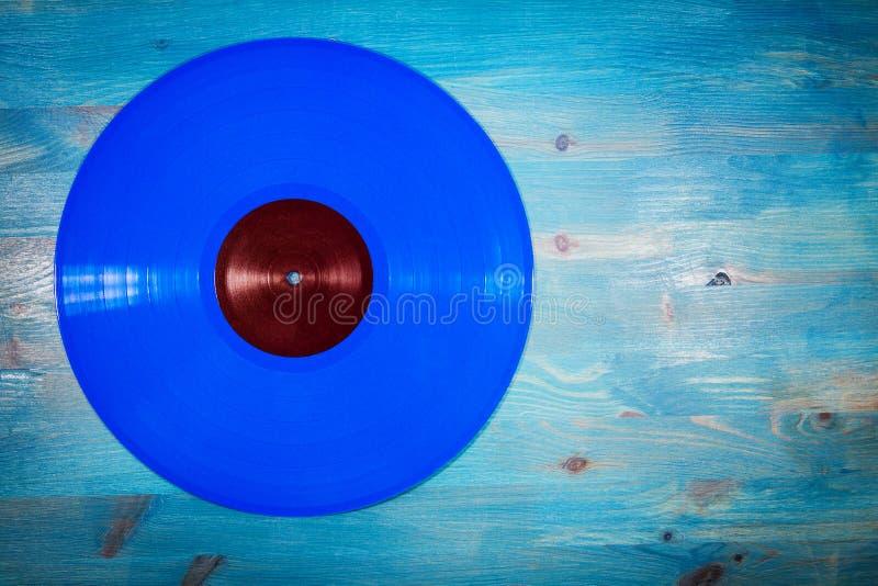 Голубой показатель винила цвета на голубой деревянной предпосылке стоковые изображения