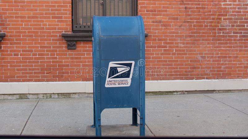 Голубой почтовый ящик USPS перед кирпичной стеной стоковые изображения