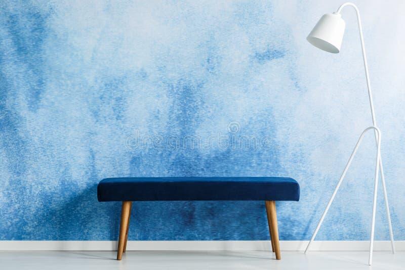 Голубой стенд и белая лампа установили на стену aquarelle в ждать roo стоковая фотография