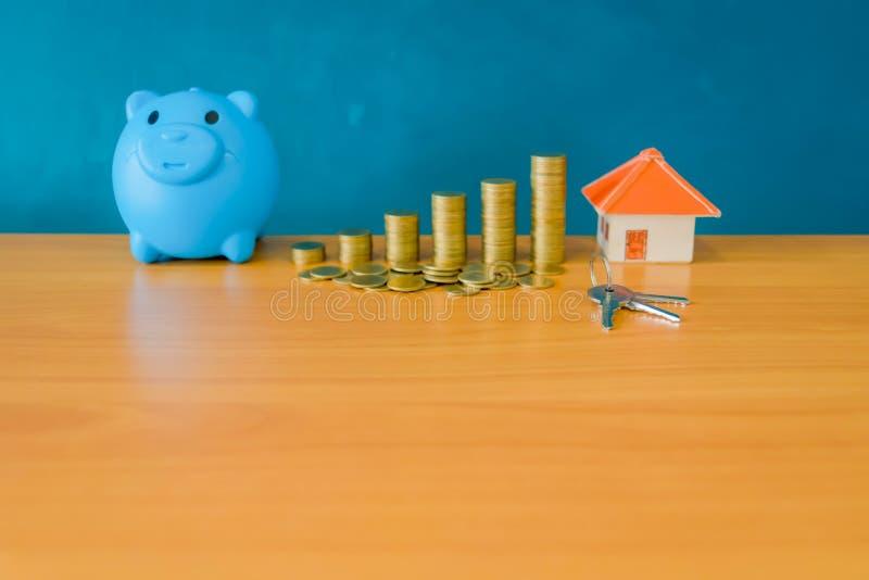 Голубой стог банка и монеток свиньи и желтый бумажный дом для денег s стоковая фотография rf