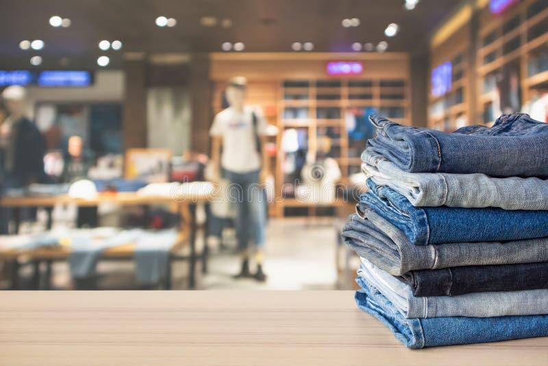 Голубой стог джинсов джинсовой ткани на деревянной столешнице стоковое изображение rf