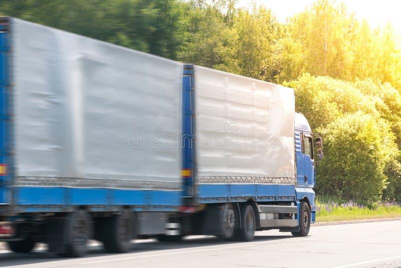 Голубой фургон доставки и белая тележка управляя на дороге асфальта между линией деревьев в ландшафте осени стоковые фото