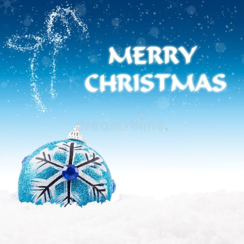 Голубой bauble на снежке с приветствием рождества стоковые изображения