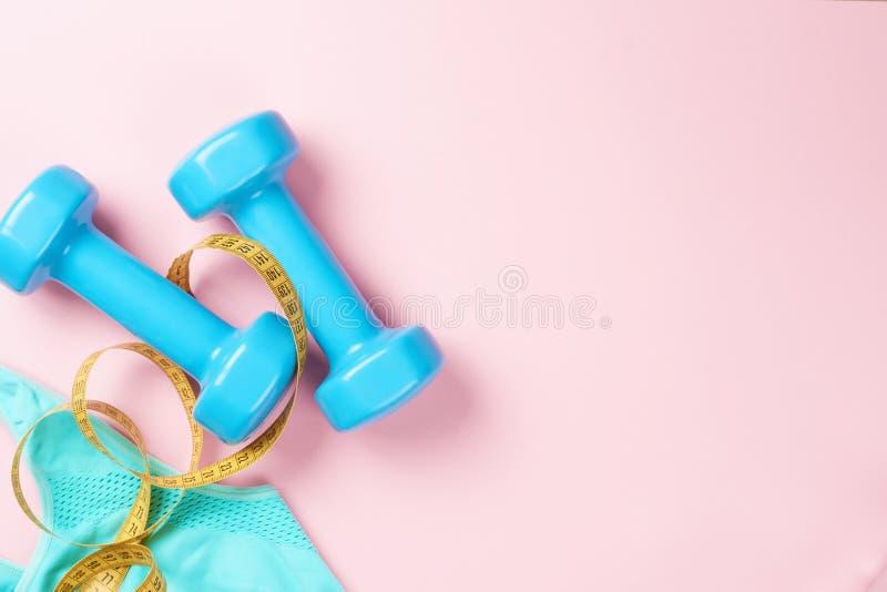 Голубые гантели и бюстгальтер на розовой предпосылке, взгляд сверху спорта с космосом экземпляра релаксация pilates пригодности п стоковое изображение rf