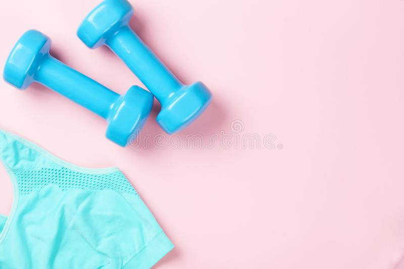 Голубые гантели и бюстгальтер на розовой предпосылке, взгляд сверху спорта с космосом экземпляра релаксация pilates пригодности п стоковые изображения rf