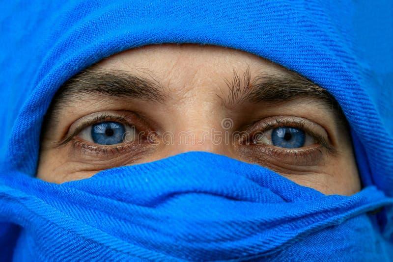 голубые глаза человека, лицо которого покрыто синим бинтом стоковые фото