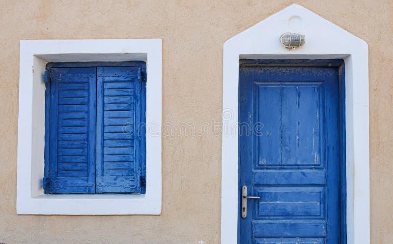 Голубые двери и окна традиционного греческого острова с белой рамой стоковые фото