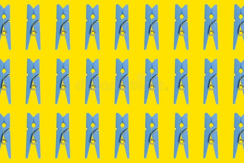 Голубые деревянные зажимки для белья на желтой предпосылке собрание Одежд-колышка Комплект голубой деревянной красочной зажимки д иллюстрация штока