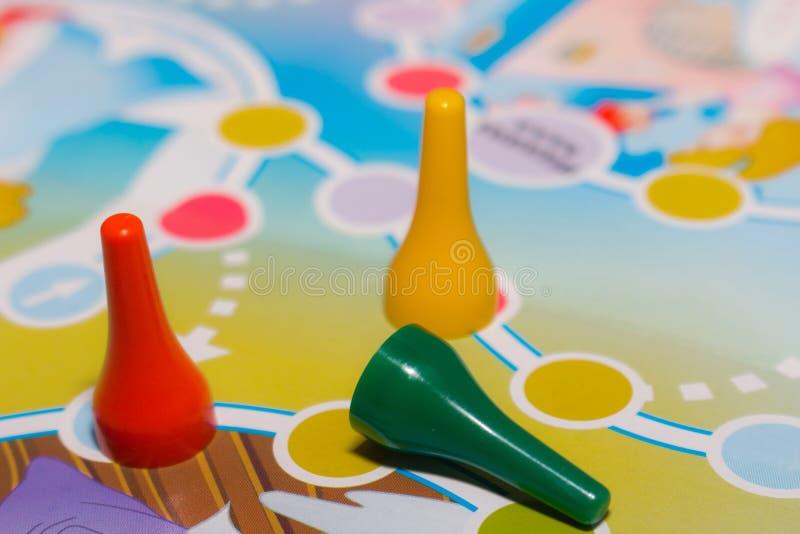 Голубые, желтые и красные пластичные обломоки, кость и настольные игры для детей стоковые изображения
