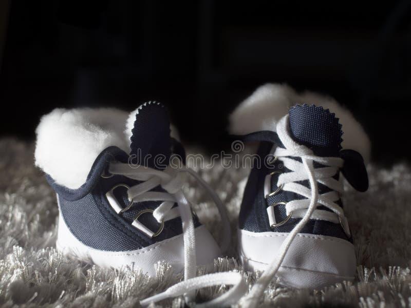Голубые и белые ботинки ` s детей на темной предпосылке стоковая фотография