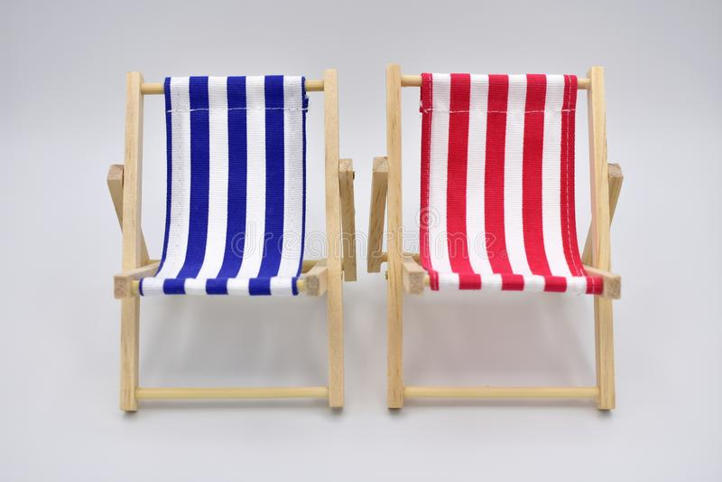 Голубые и красные шезлонги изолированные на белой предпосылке стоковая фотография rf