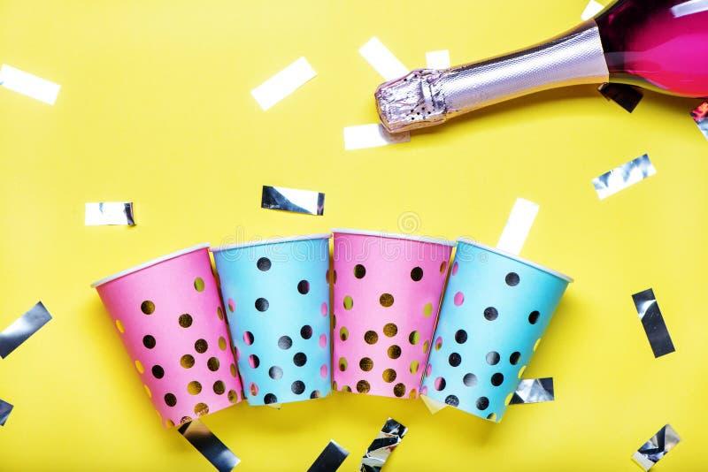 Голубые и розовые бумажные стаканчики точки польки на желтой предпосылке стоковое изображение