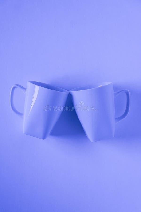 Голубые кружки кофе на голубой предпосылке clinking в приветственных восклицаниях с пустым copyspace стоковые изображения rf