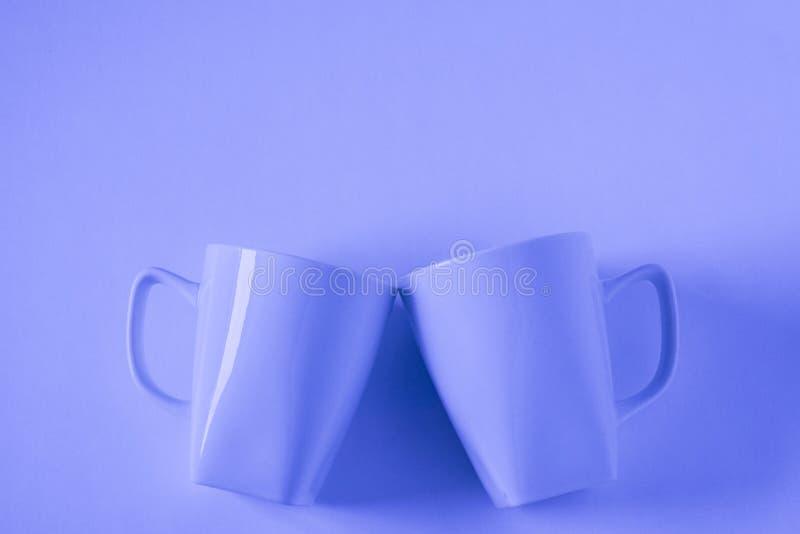 Голубые кружки кофе на голубой предпосылке clinking в приветственных восклицаниях с пустым copyspace стоковое изображение