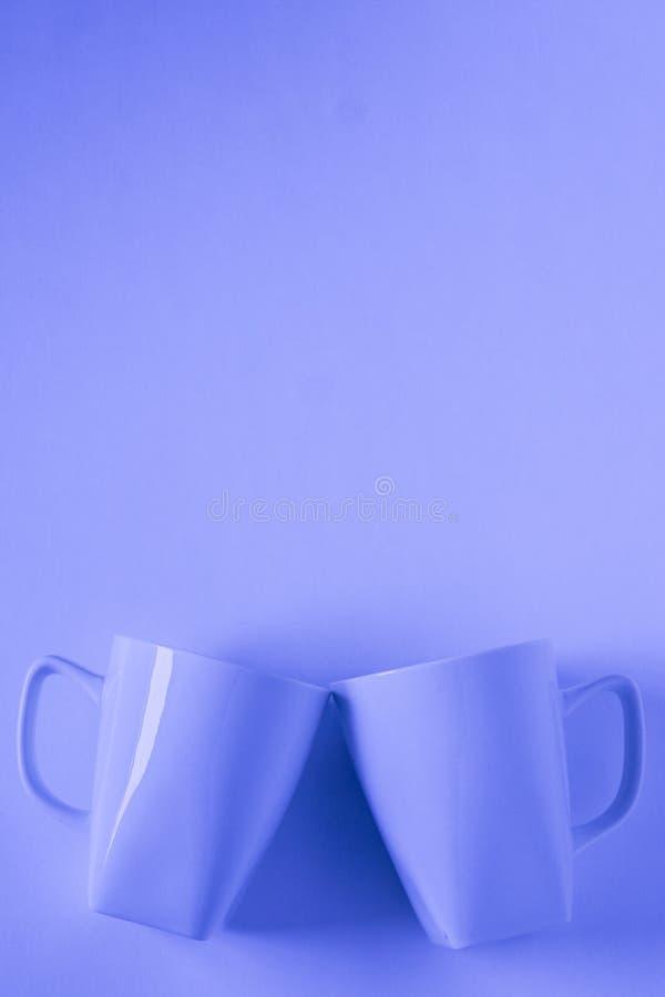 Голубые кружки кофе на голубой предпосылке clinking в приветственных восклицаниях с пустым copyspace стоковое фото rf