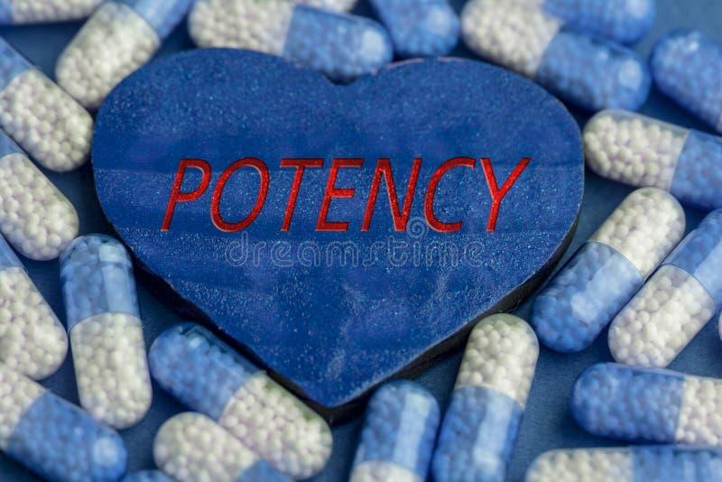 Голубые медицинские капсулы и голубое сердце с красной надписью: МОЩЬ стоковые фото