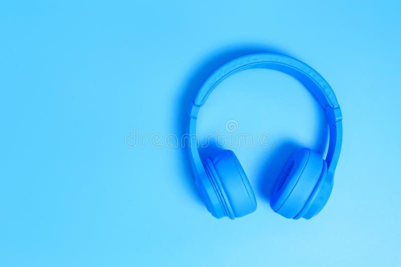Голубые наушники, взгляд сверху наушников на голубой предпосылке Минималистское фото наушников с космосом экземпляра Белые наушни стоковые изображения rf