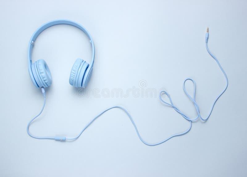 Голубые наушники с кабелем на серой предпосылке стоковое изображение rf