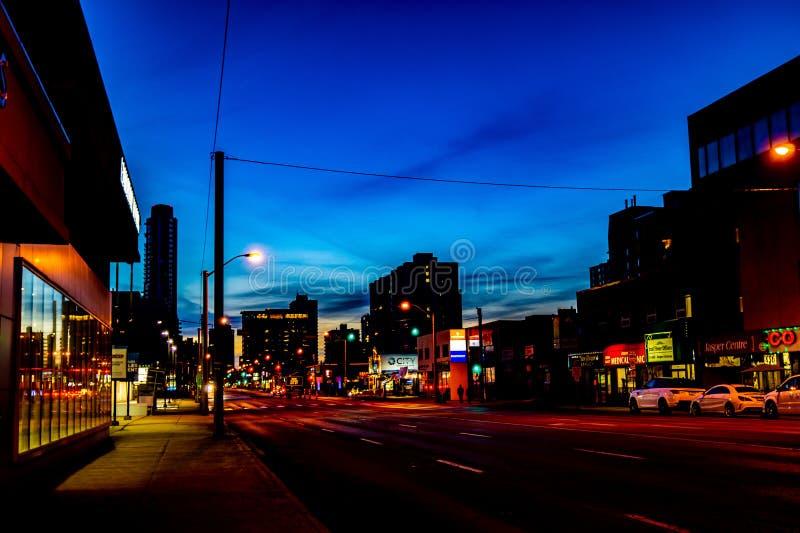 Голубые небеса как падения и город ночи приходят живой стоковые изображения rf